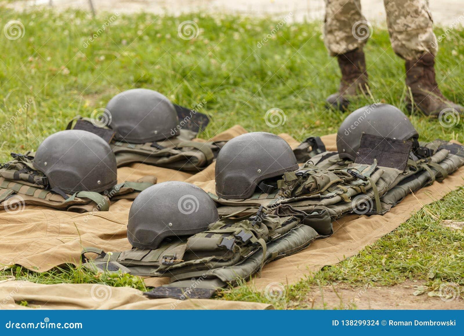 Camufle las chaquetas y los cascos de fuego antiaéreo del combate alineados en la tierra