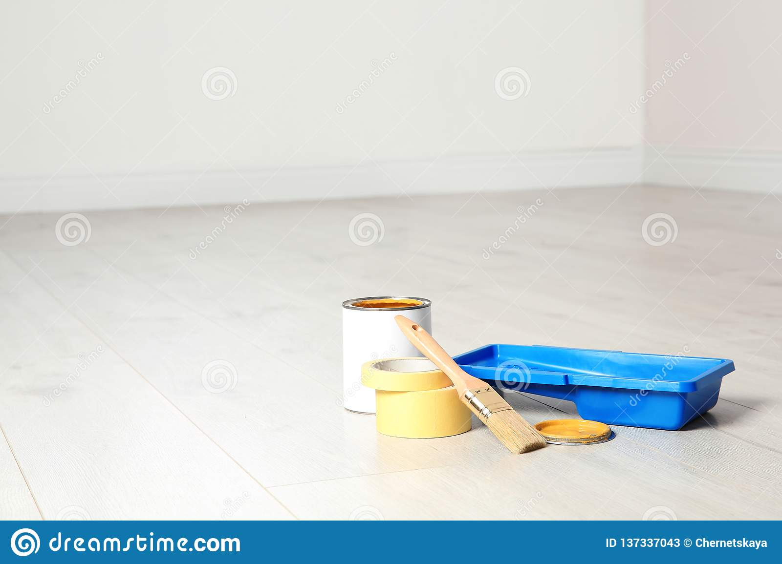 Can of paint and decorator tools on wooden floor indoors.