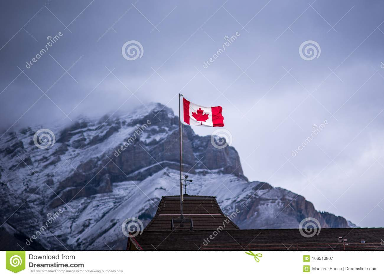 Canadian flag against snowy rocky mountain