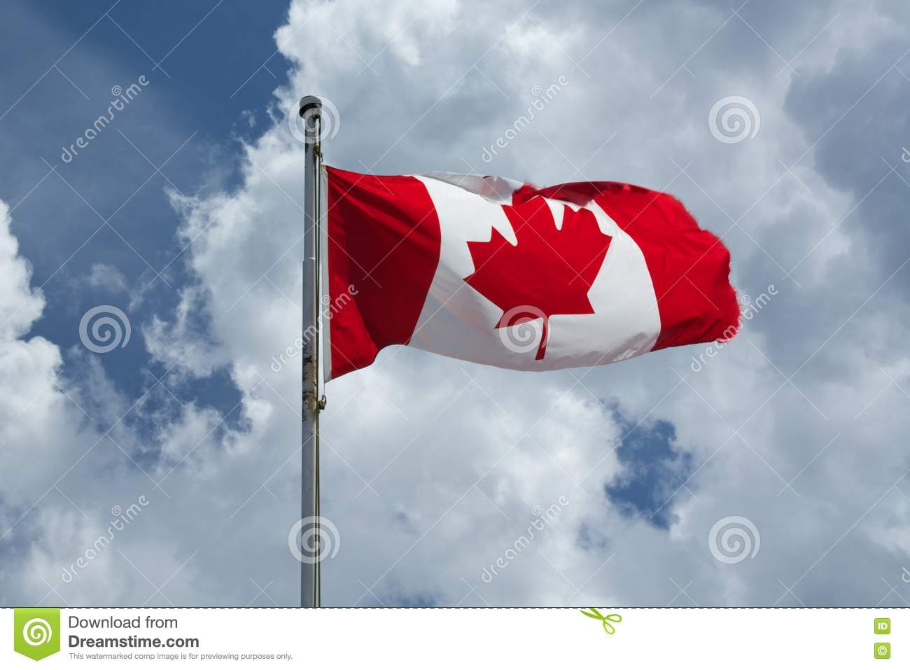 Canadian Flag flies proudly against a blue cloudy sky