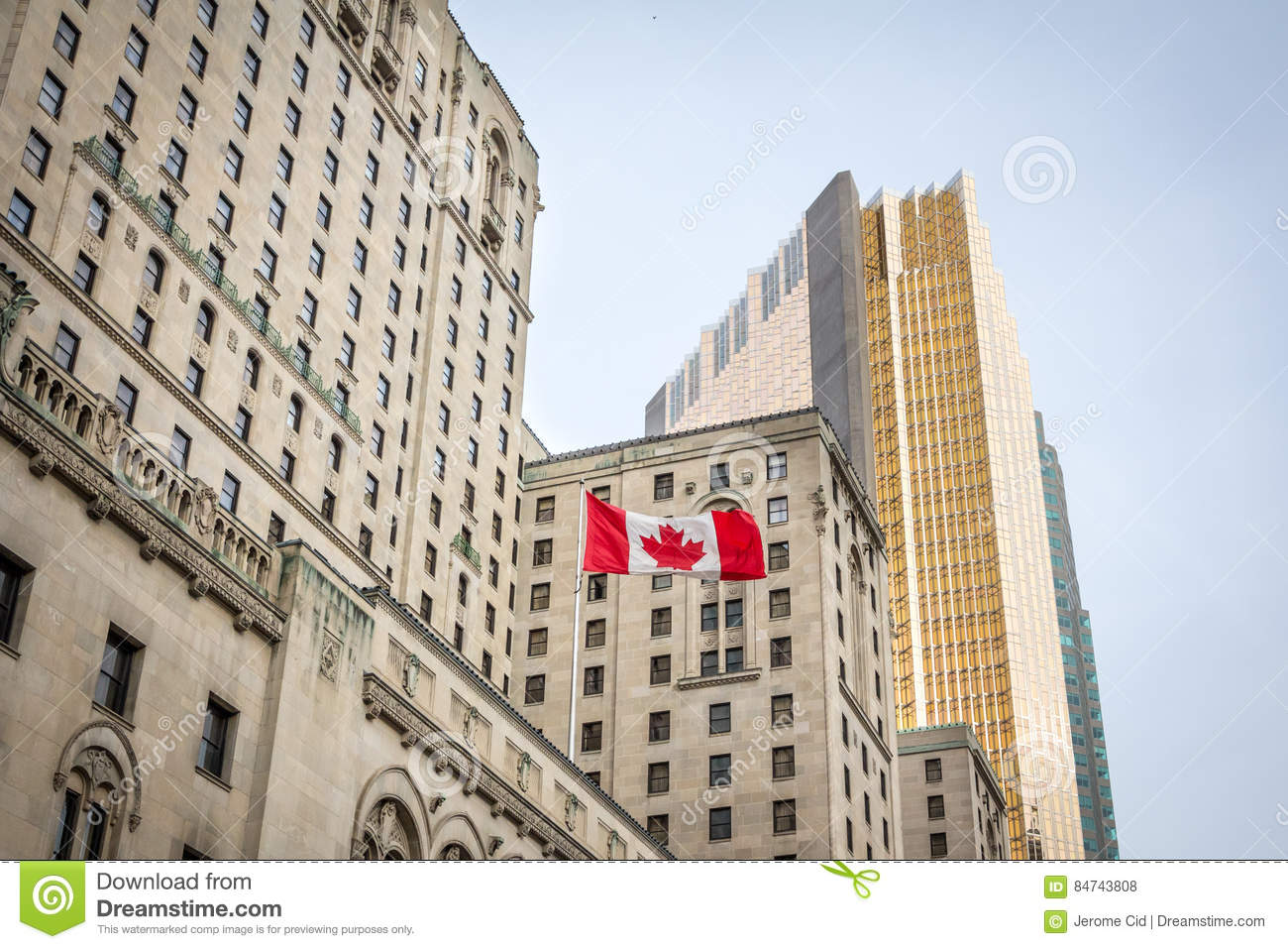 Canadian flag in front of a business building and an older skyscraper in Toronto, Ontario, Canada