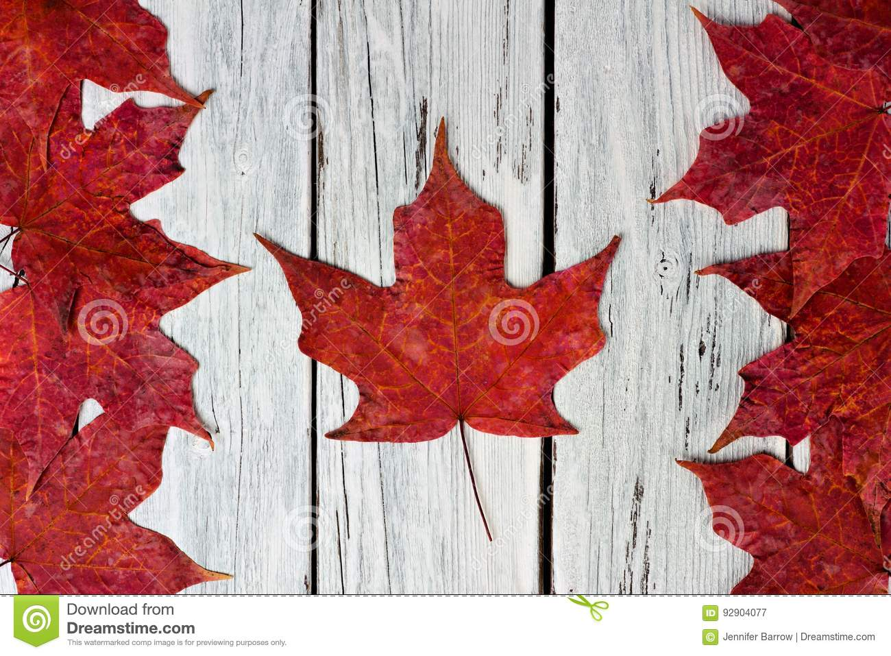 canadian flag of red maple leaves over weathered white wood stock