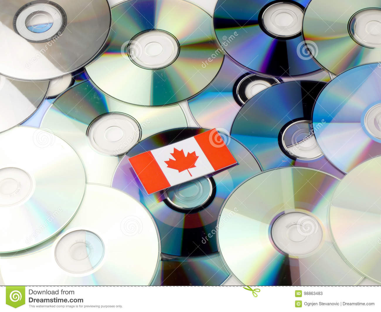 Canadian flag on top of CD and DVD pile isolated on white