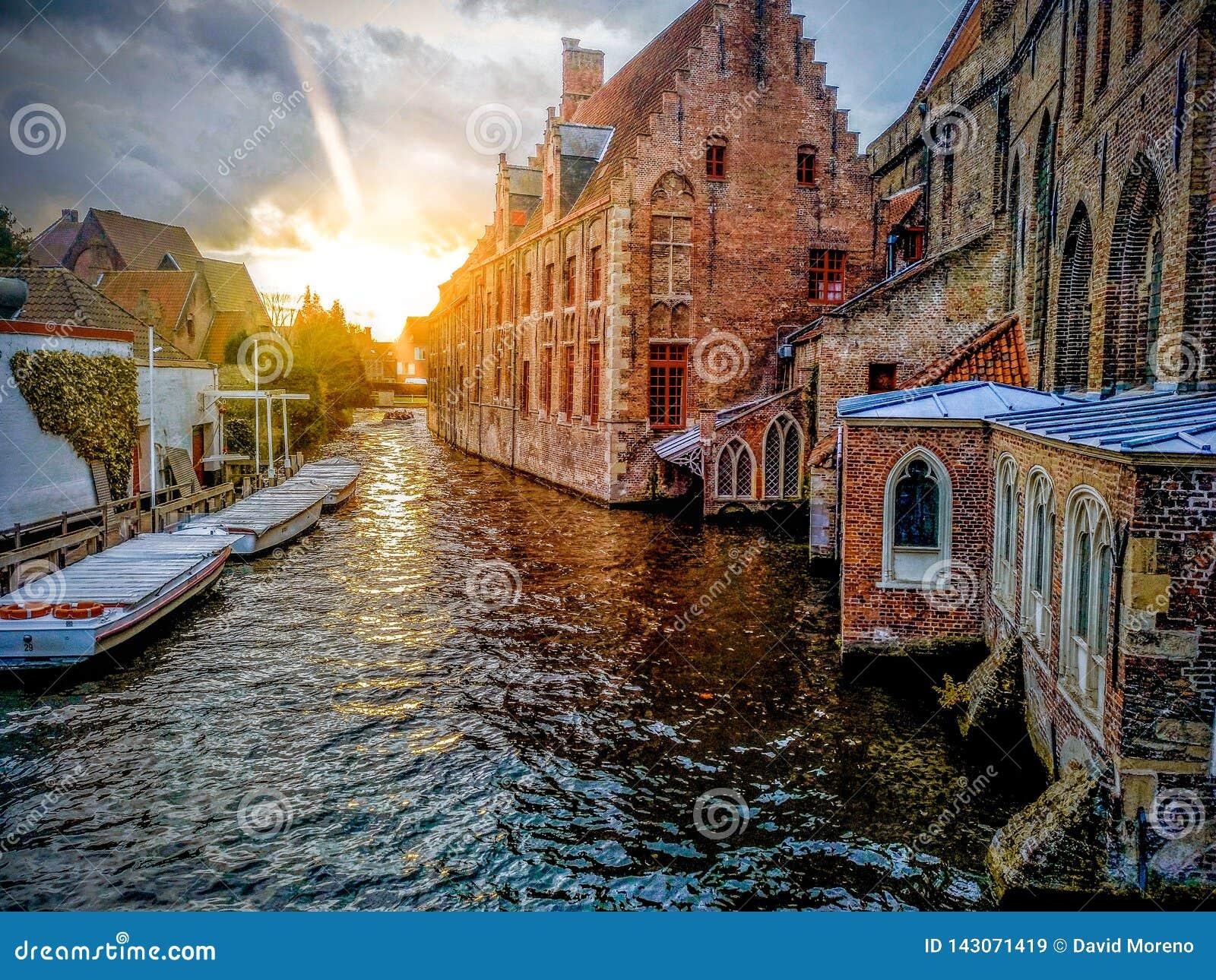 Canais da cidade medieval de Bruges usando os barcos típicos sobre canais em Bélgica