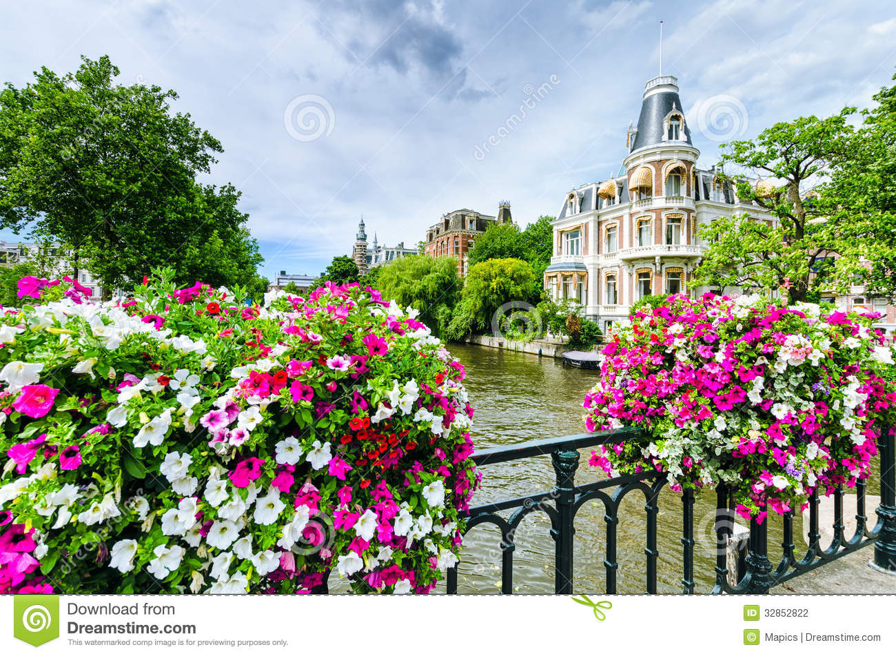 Canal In Amsterdam With Flowers On A Bridge Stock