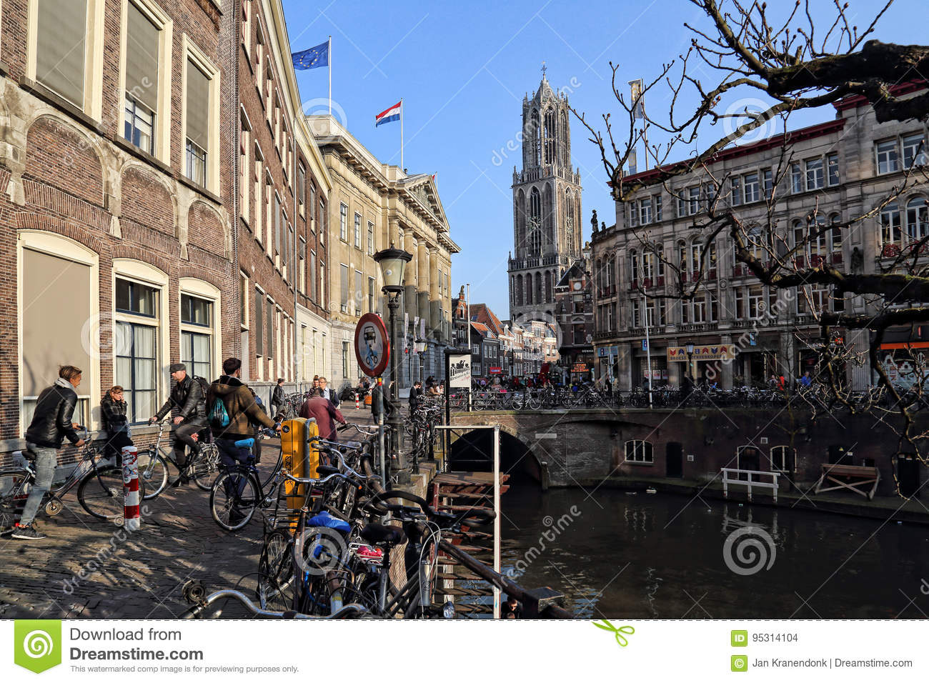 Utrecht, The Netherlands - March 16, 2017: People sit at restaurants on a  canal with Dutch flags and the church tower in the background in Utrecht,  ...
