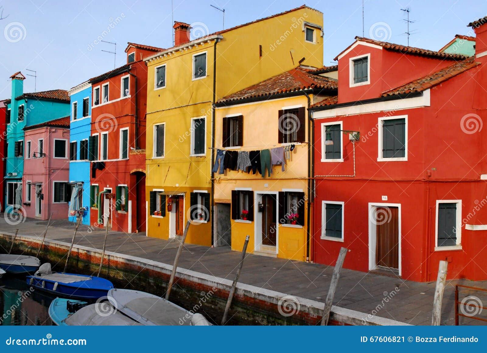 Canal com barcos e casas de muitas cores e roupa a secar em Burano em Veneza em Itália