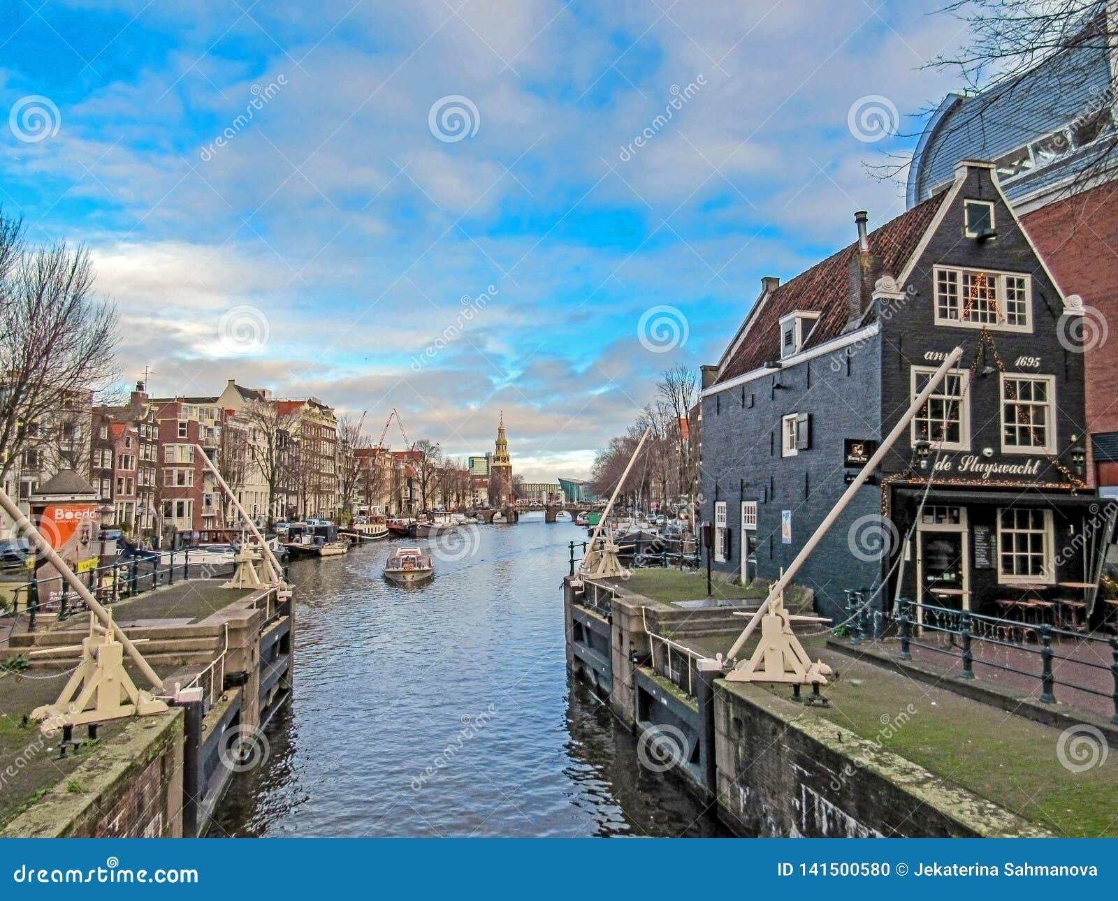 Canal da cidade em Amsterdão com barcos e casas do tijolo que refletem na água