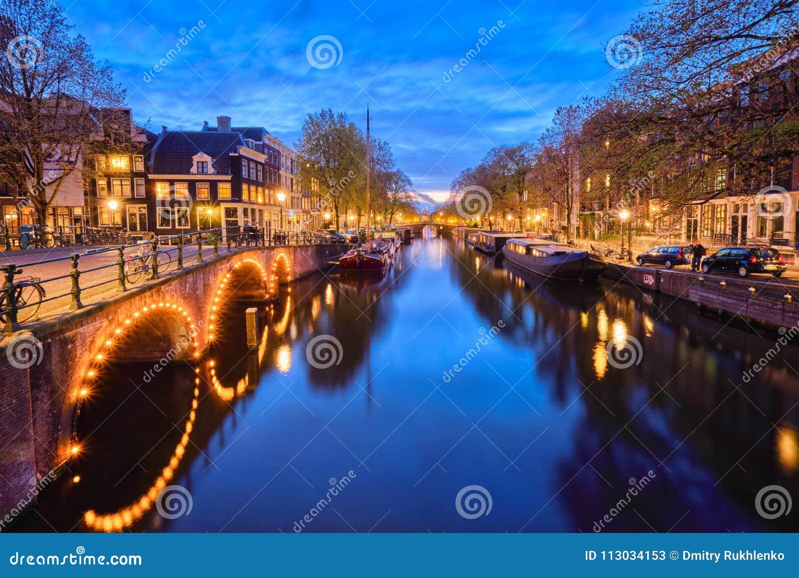 Canal de Amterdam, puente y casas medievales por la tarde