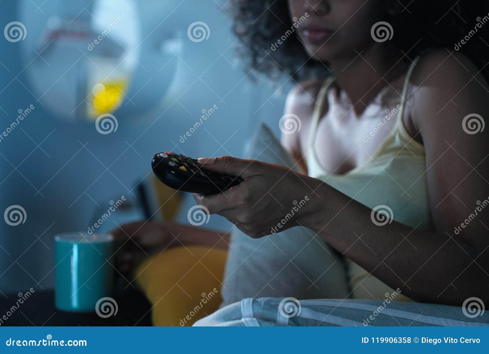 Canal de televisão em mudança da mulher negra com o telecontrole na noite
