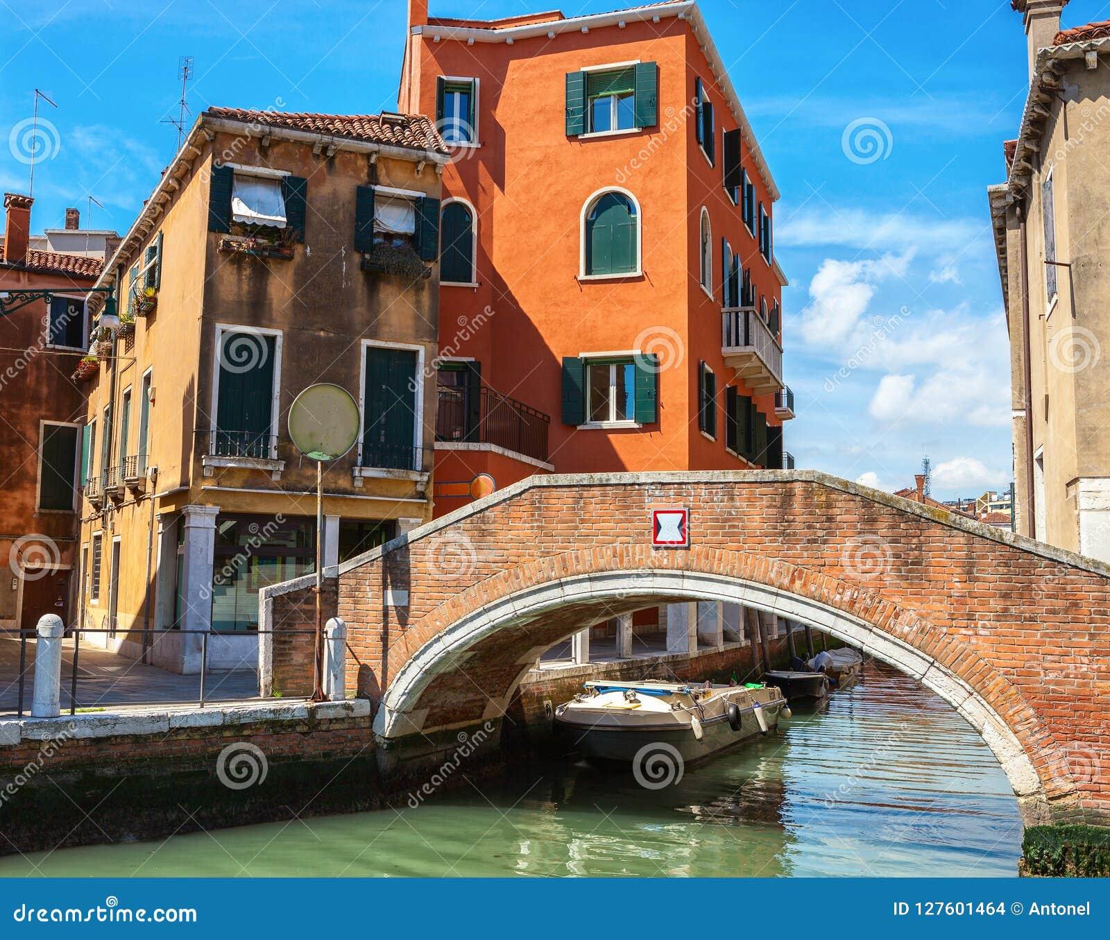 Canal veneciano entre los edificios viejos y la pequeña pasarela del ladrillo en el primero plano, Italia