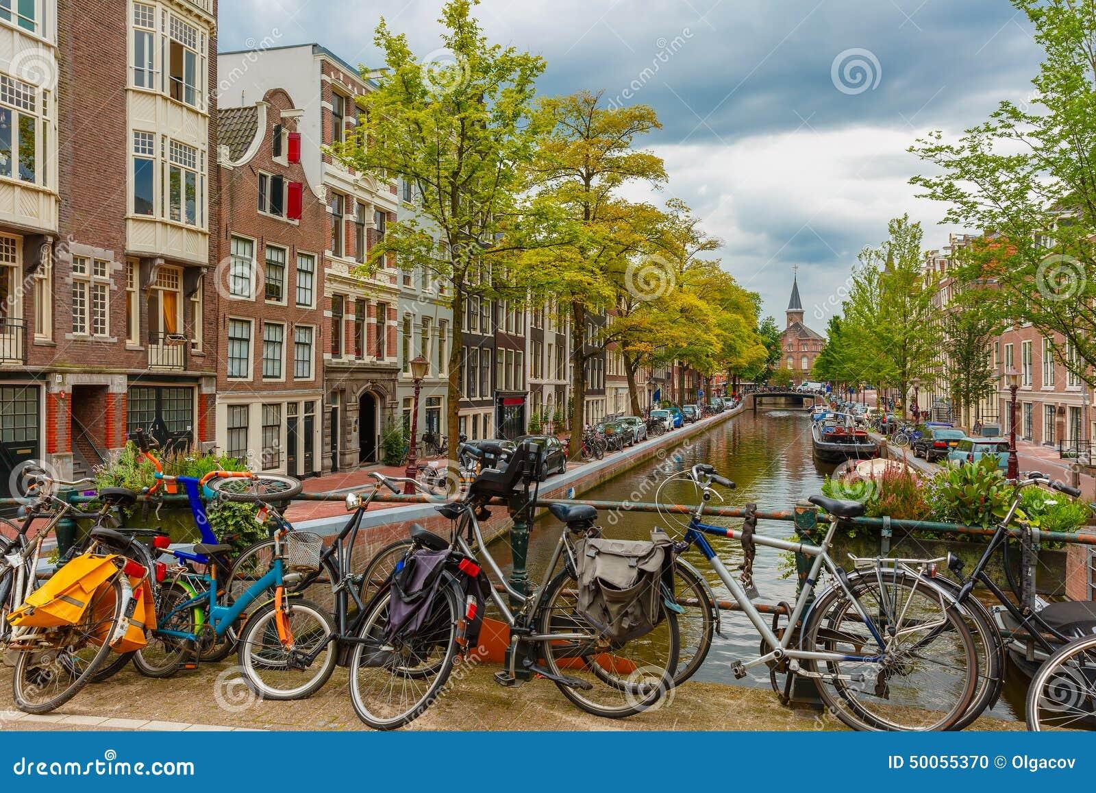 canale di amsterdam e ponte con le bici olanda fotografia