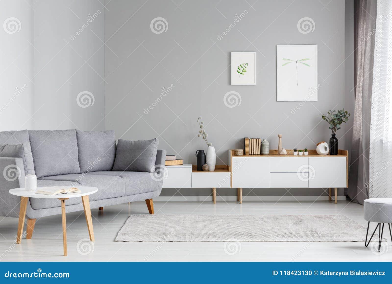 Canapé cinzento perto do armário branco no interior mínimo da sala de visitas