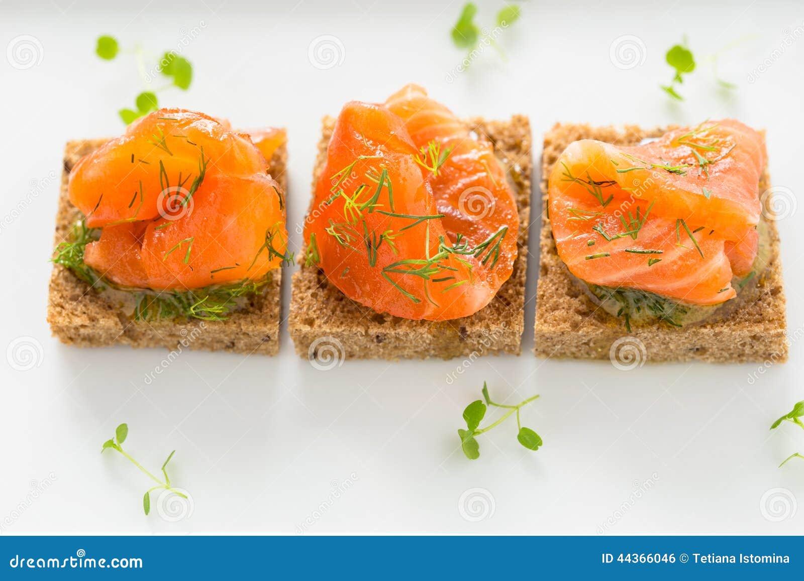 Canape deliziose dell aperitivo di pane nero con il salmone affumicato