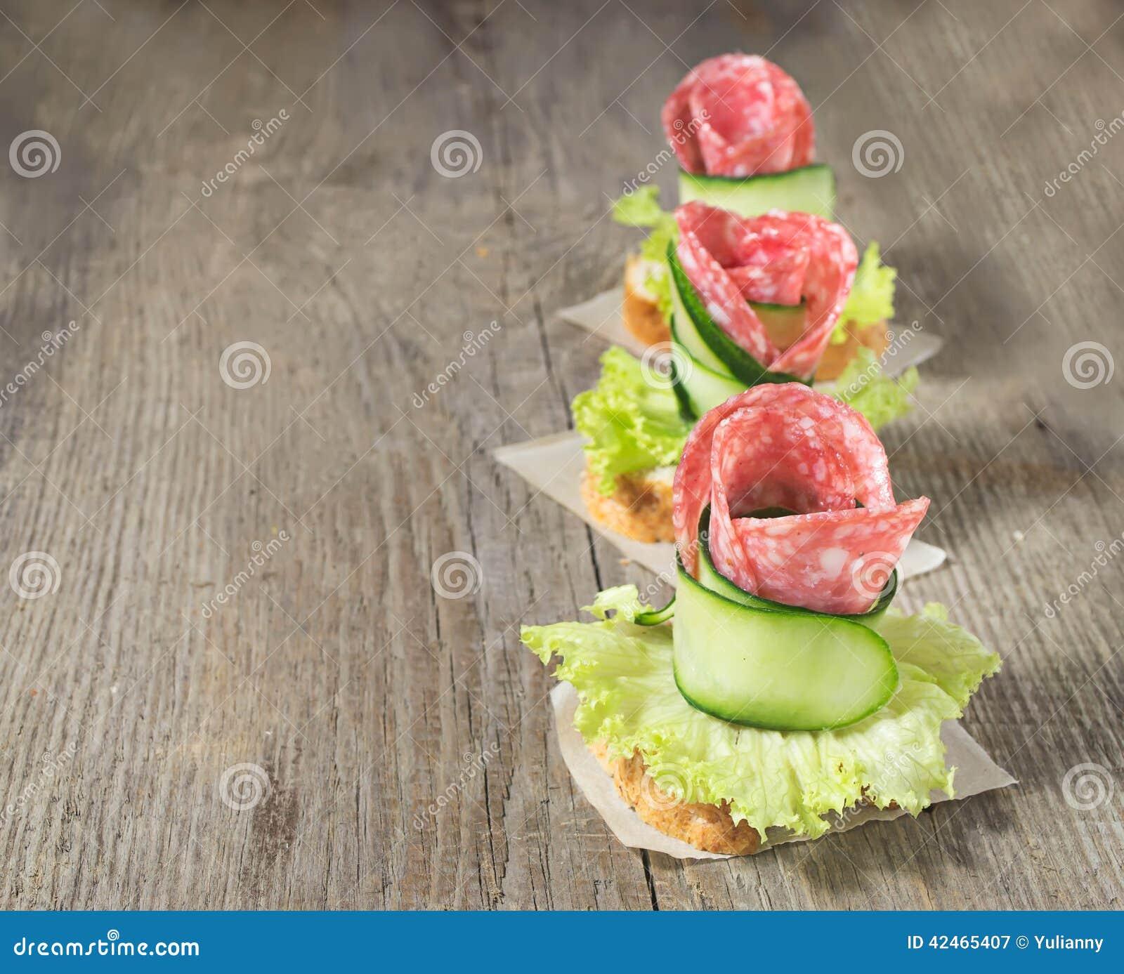 Canape mit Salami, Gurke und Salat auf Holztisch