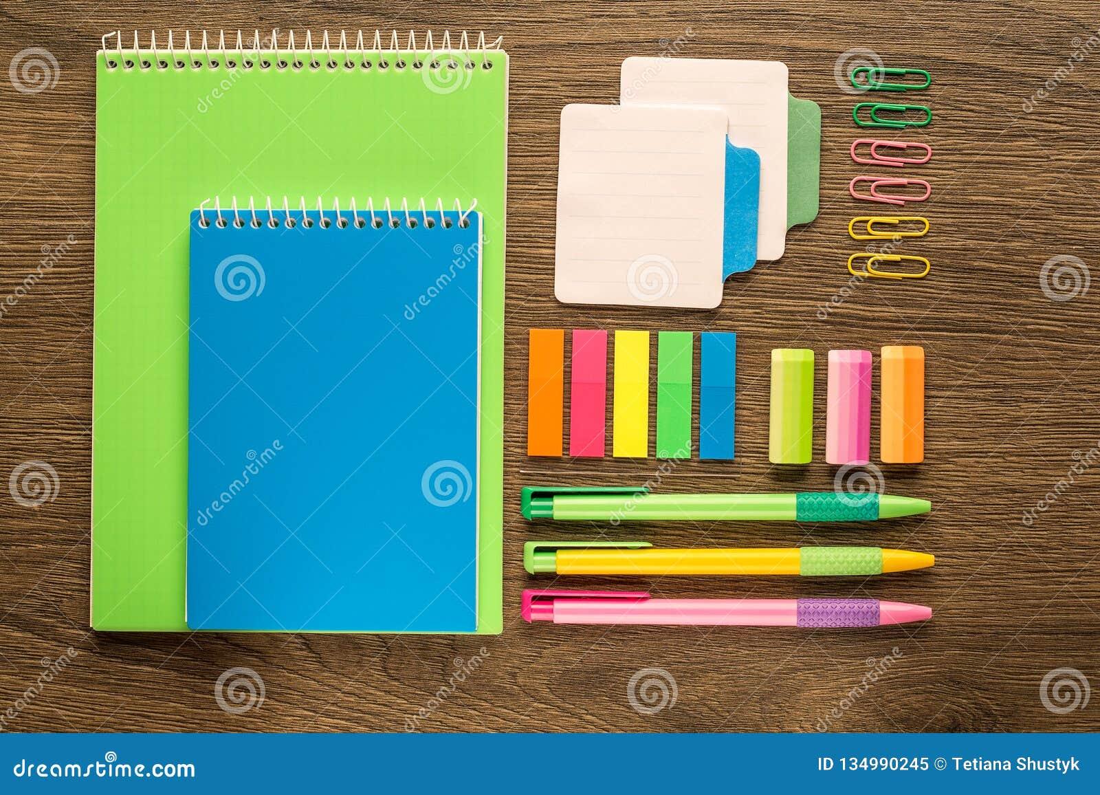 Cancelleria dell ufficio e della scuola su fondo di legno Taccuino, blocco note, penna, matite e roba Vista superiore Flatlay