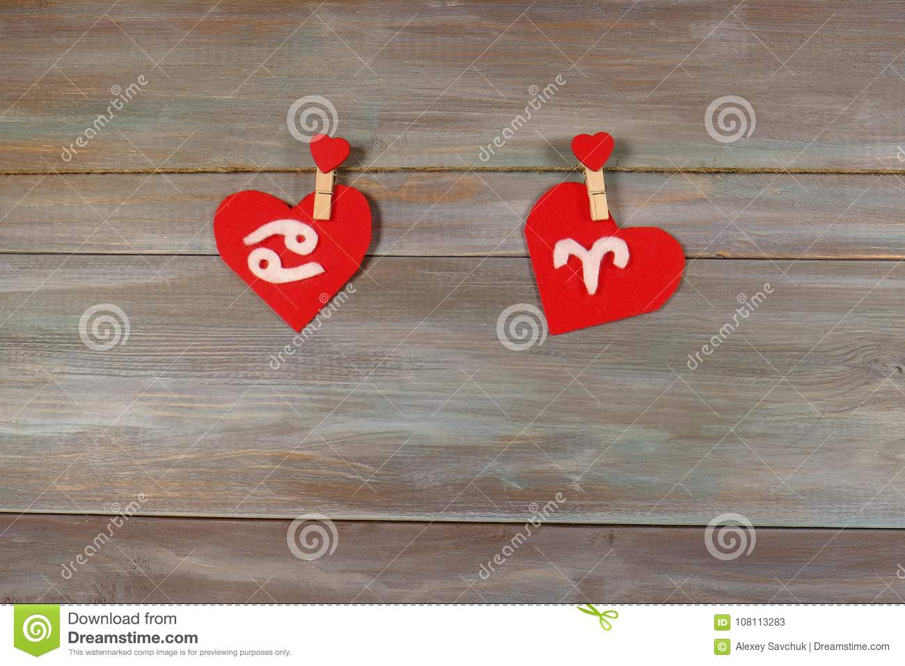 Cancer and Aries. signs of the zodiac and heart. wooden backgrou