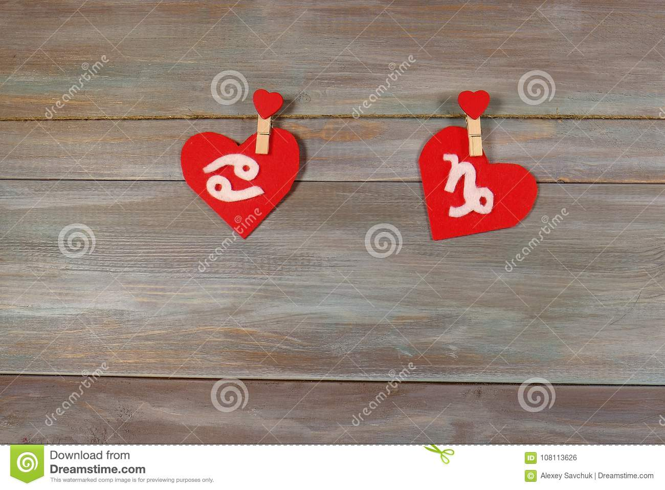 Cancer and Capricorn. signs of the zodiac and heart. wooden back