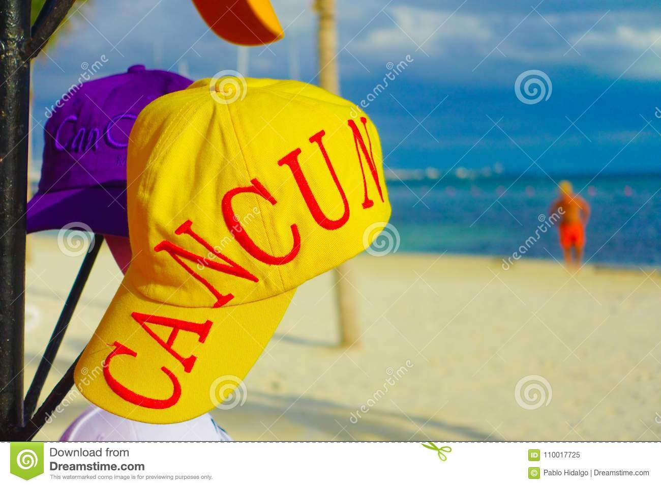 CANCUN, MEXICO - JANUARY 10, 2018: Close up of a yellow sport hat with a Cancun word printed, with a gorgeous white sand