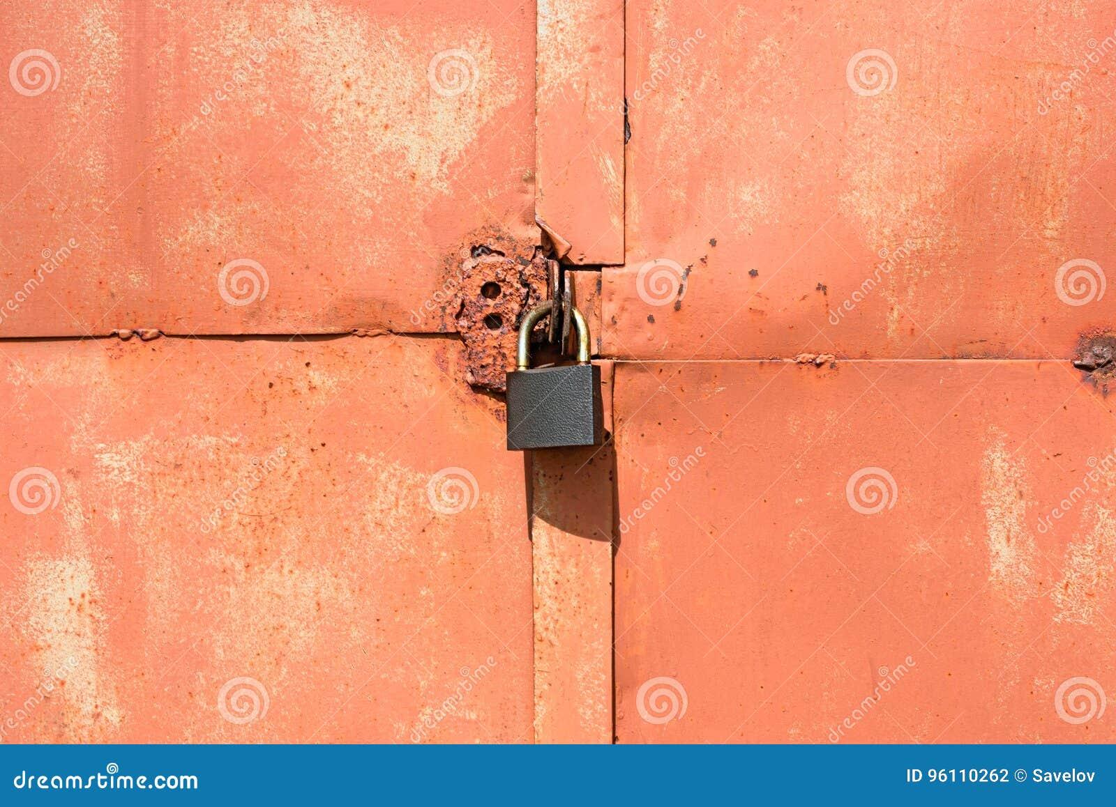 Candado en una puerta anaranjada vieja del garaje