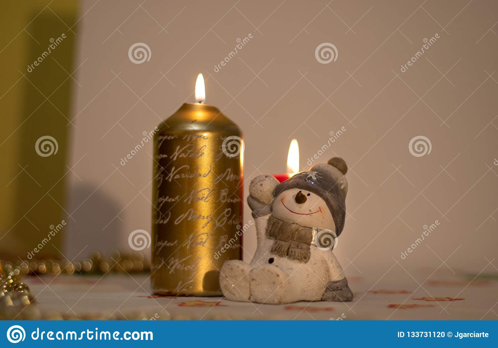 Candela di Natale con una figura di un pupazzo di neve sveglio