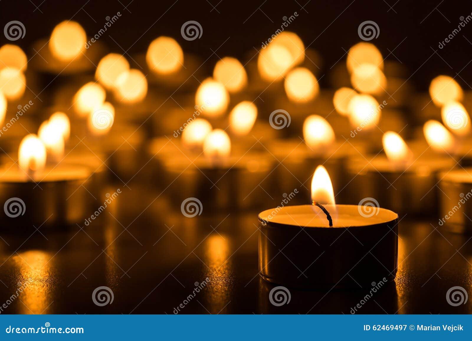 Candele di Natale che bruciano alla notte L estratto esamina in controluce la priorità bassa Luce dorata della fiamma di candela