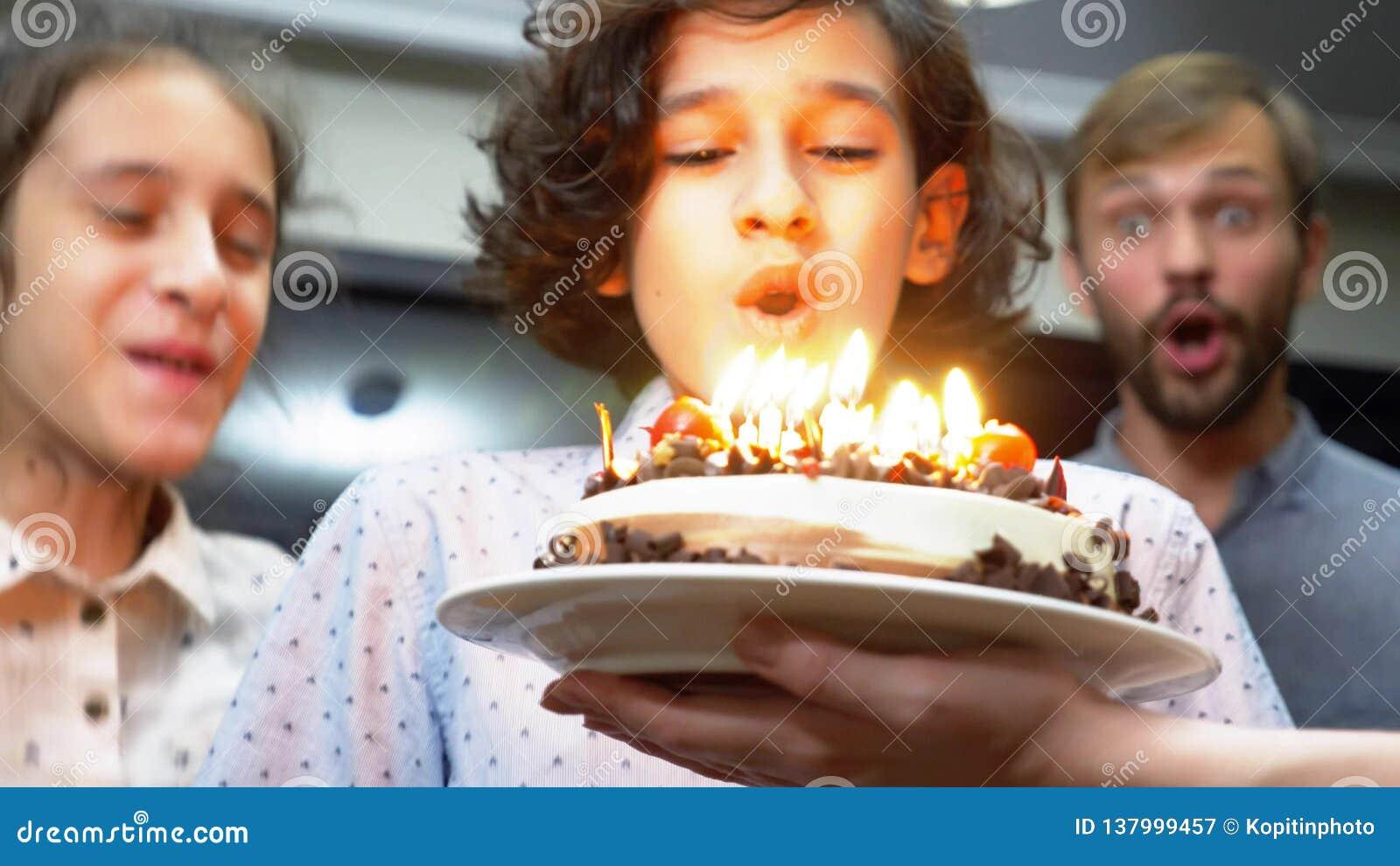 Candele di salto sorridenti felici del ragazzo sulla sua torta di compleanno bambini circondati dalla loro famiglia Torta di comp