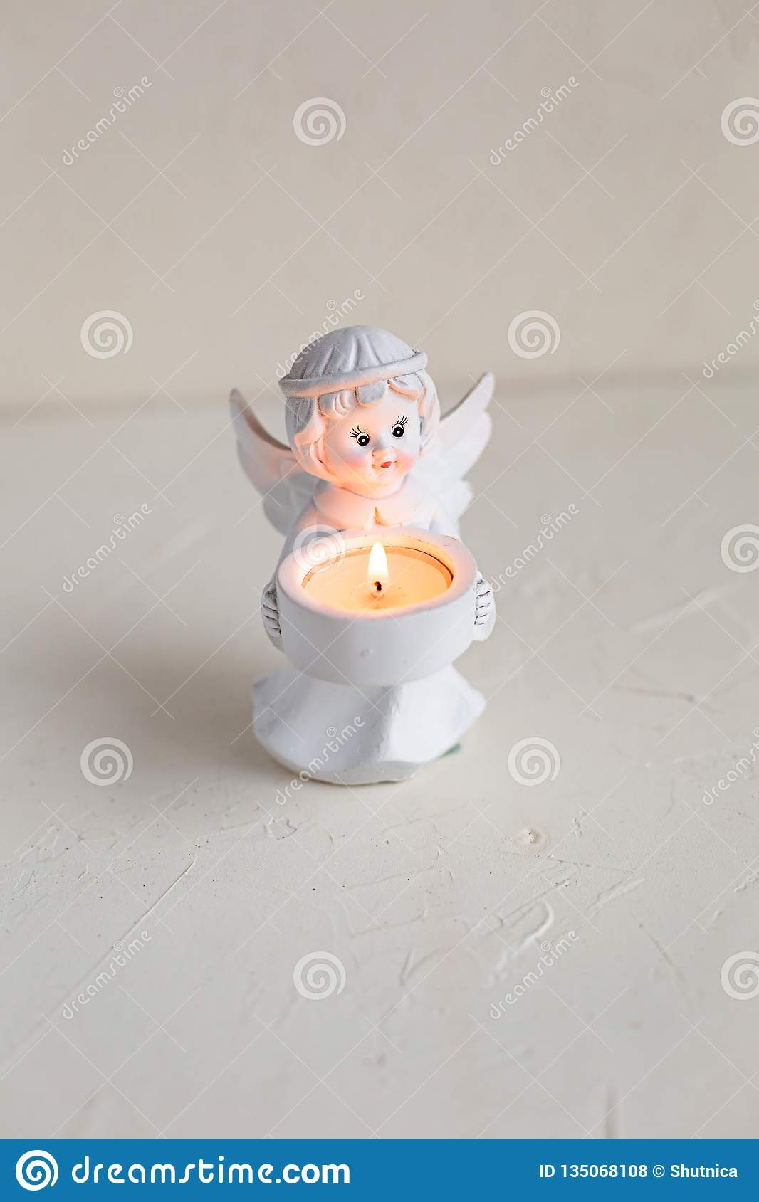 Candelero blanco del ángel con la vela encendida en blanco