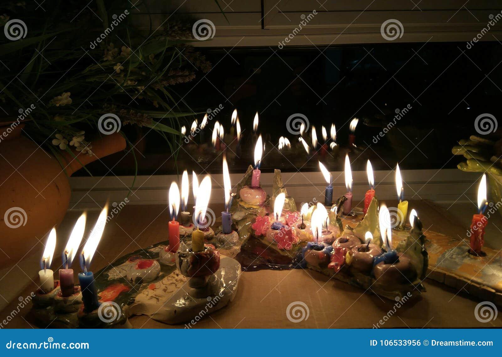 Candeles de Hanukkah encendidos en un estante de la ventana