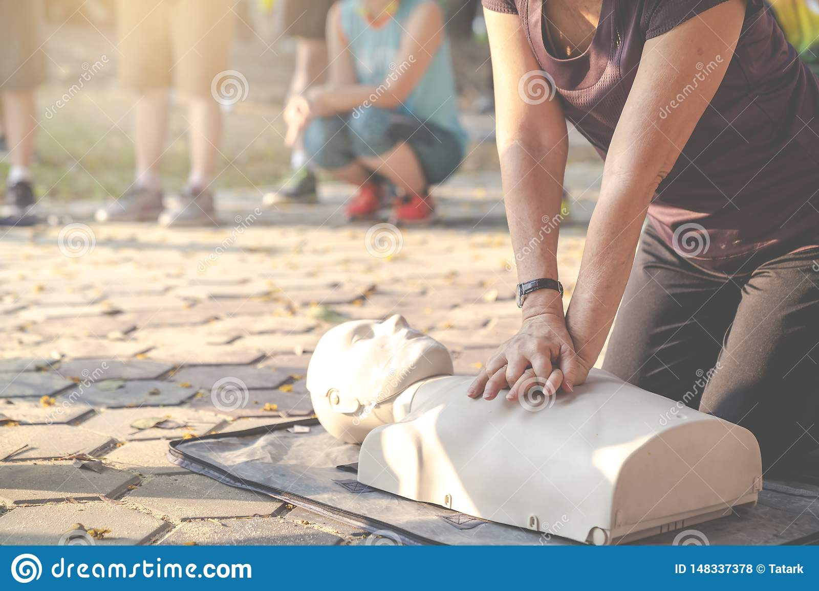 Candid of mature asian female or older runner woman training on CPR demonstrating class in outdoor park and put hands over CPR