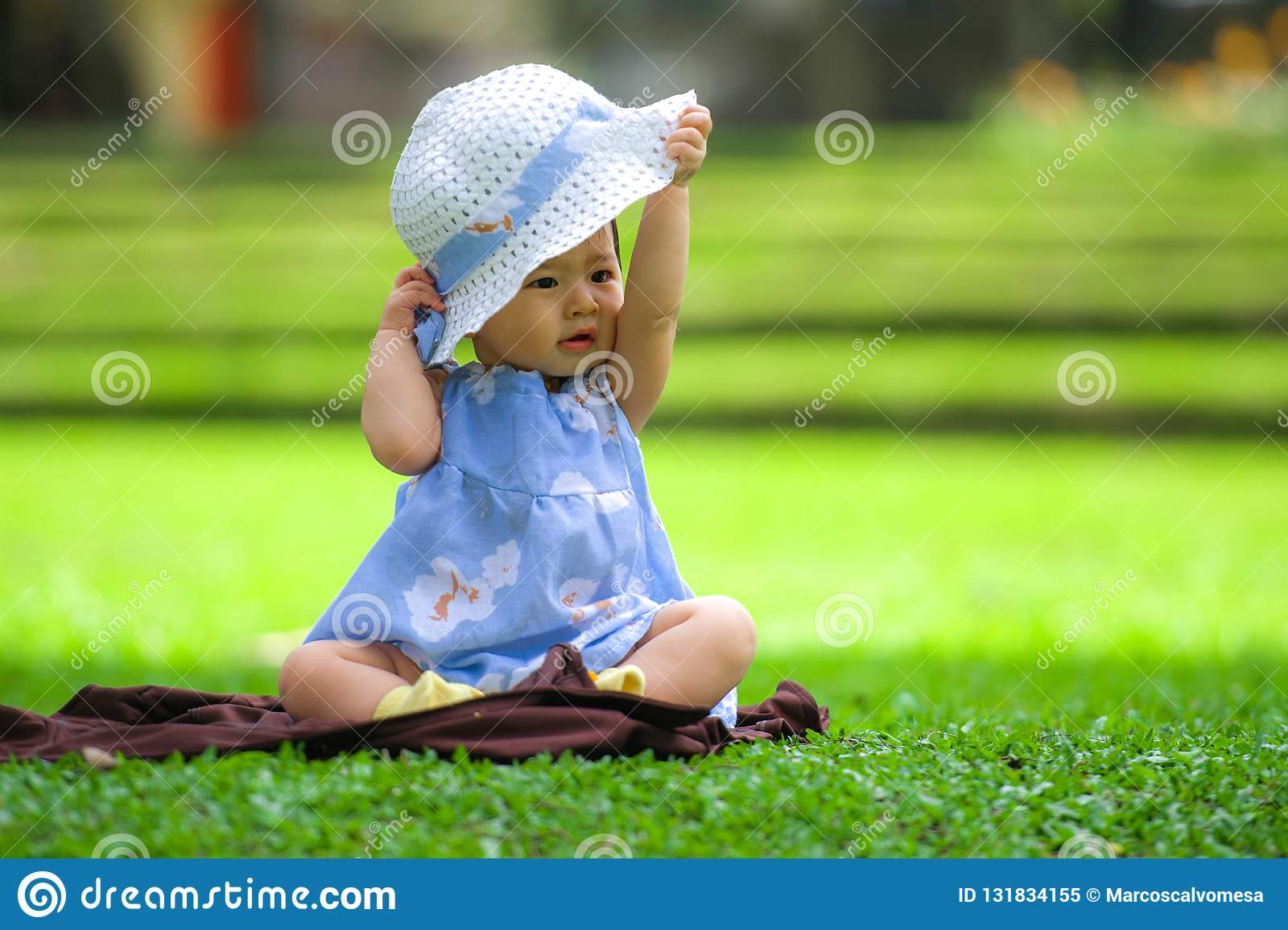 candid portrait of sweet and adorable Asian Korean baby girl 3 or 4 months old playing with hat alone at city park