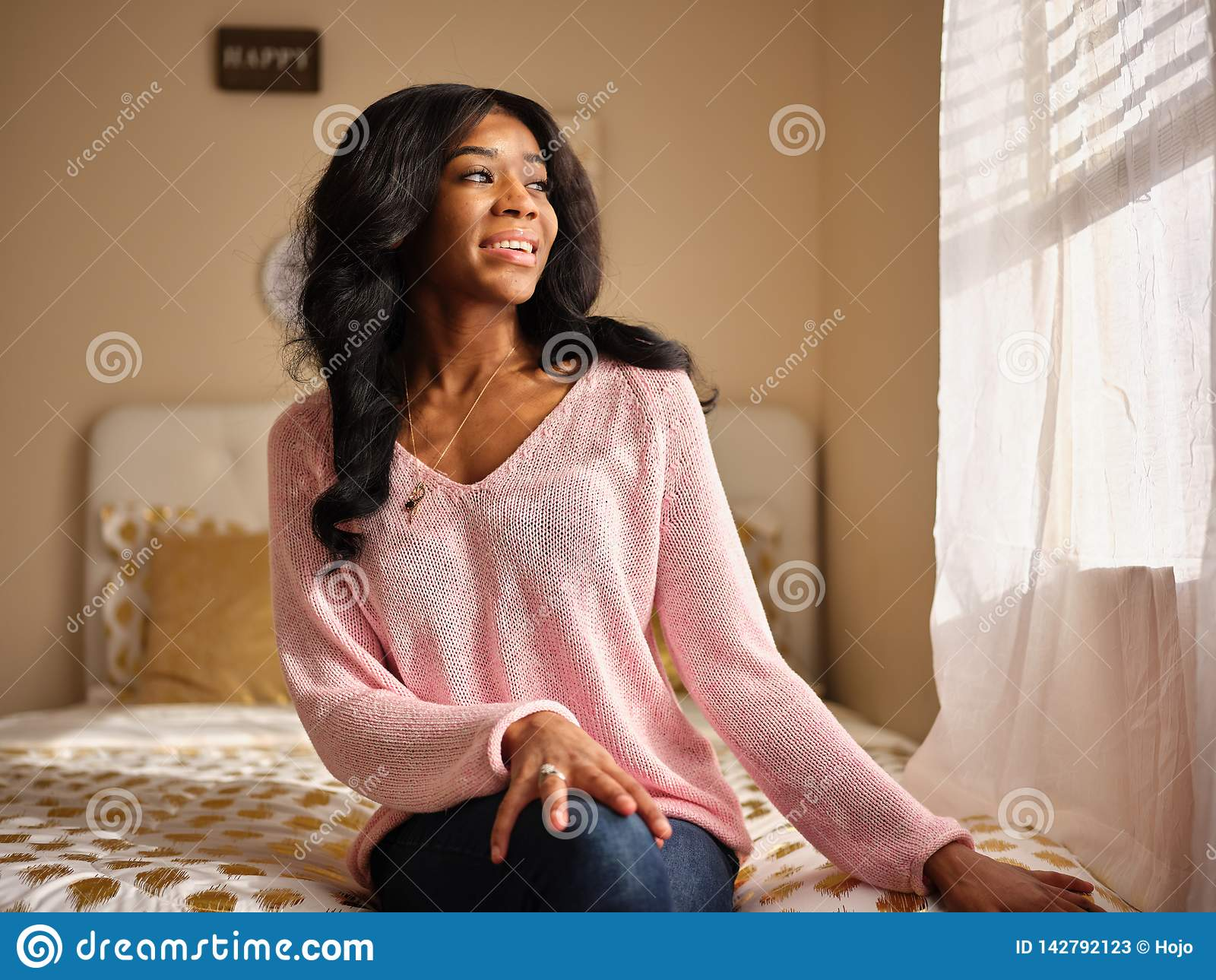 Candid portrait of young african american woman wearing pink sweater