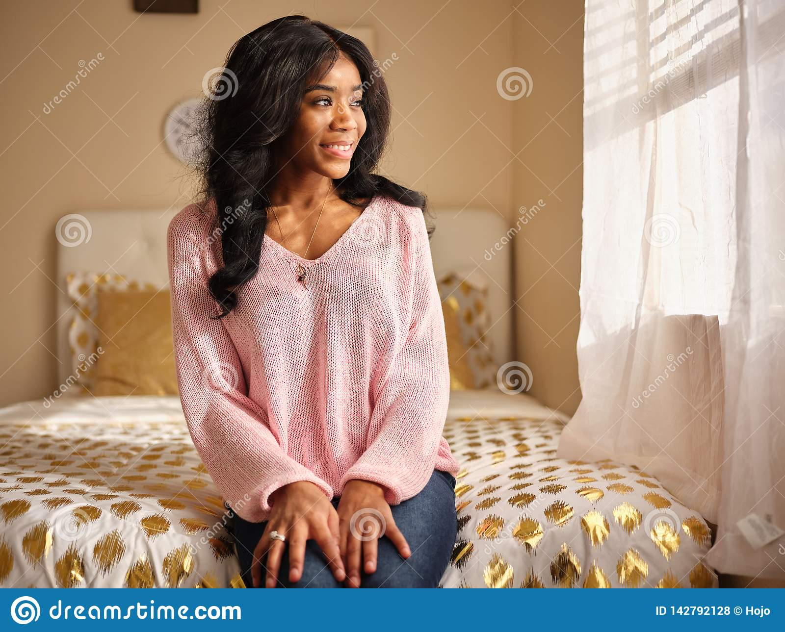 Candid portrait of young african american woman wearing pink sweater sitting on bed at home