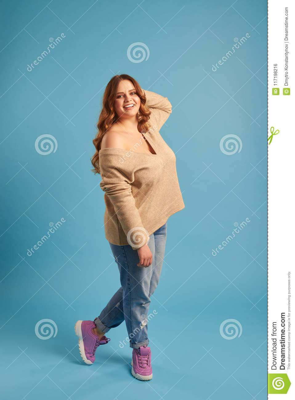Candid young plus-size girl posing against blue background