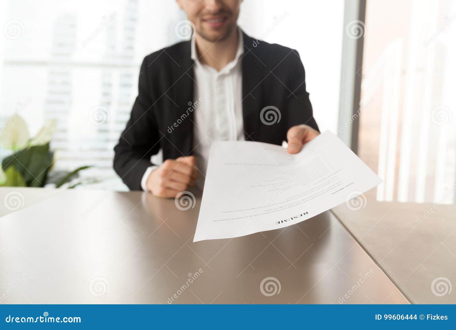 Candidato de trabajo sonriente que entrega el curriculum vitae al reclutador durante adentro