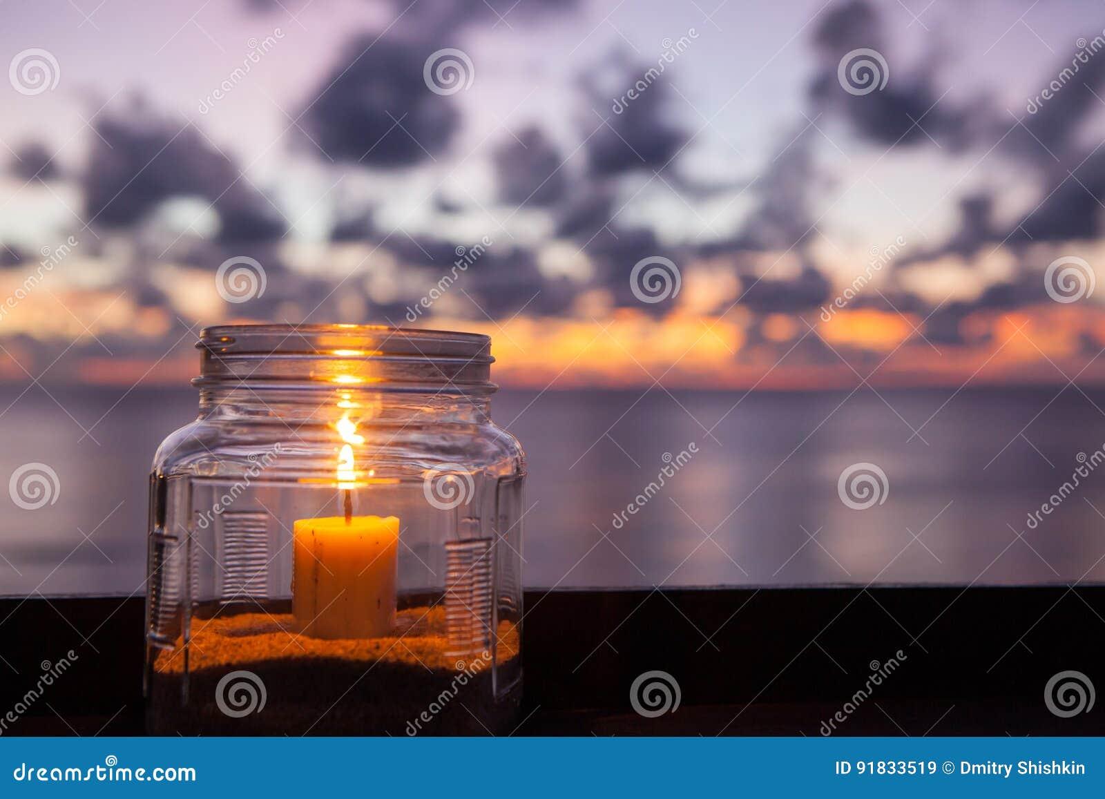 Candle a lâmpada na tabela com mar e fundo do por do sol