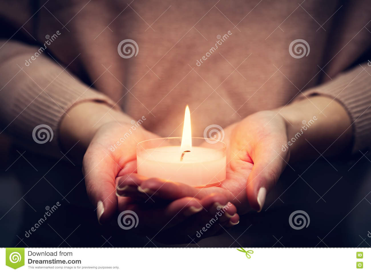 Candle light glowing in woman s hands. Praying, faith, religion