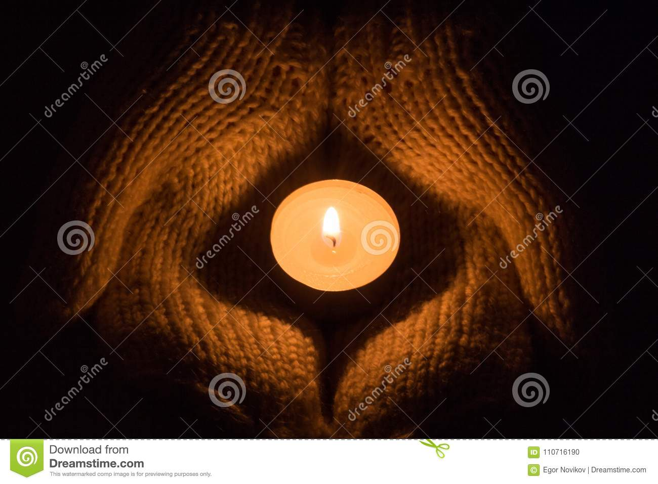Candle light glowing in woman`s hands. Praying, faith, religion concept.