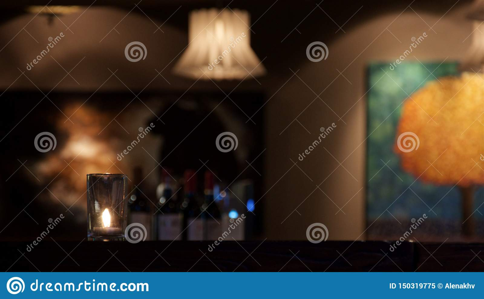 The candle stands on the table in the muffled light in the restaurant
