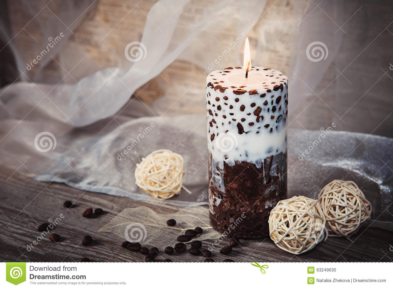Candlelight. Beautiful handmade candle and whiteTwig Balls on old wooden texture background