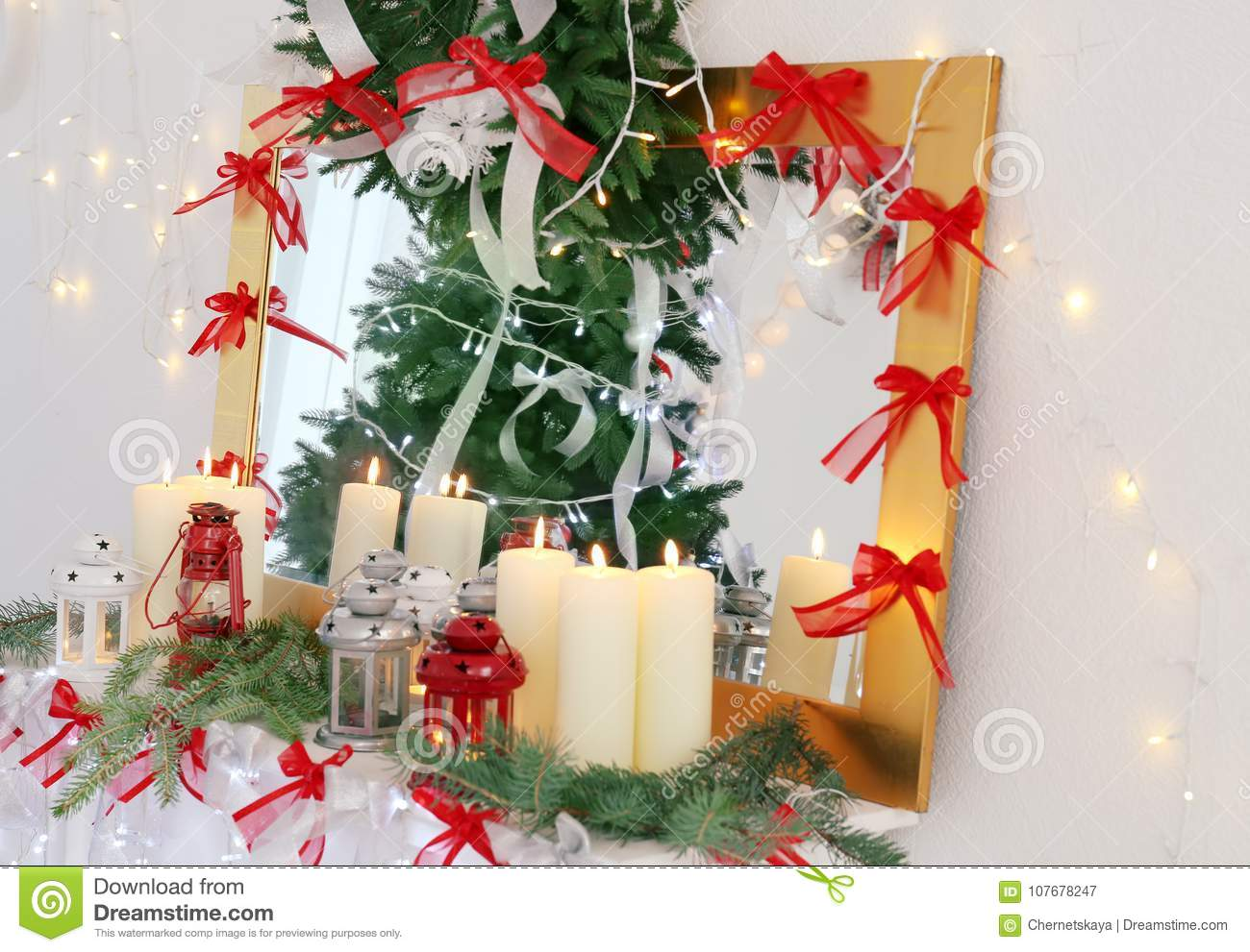 candles and christmas decorations on mantelpiece