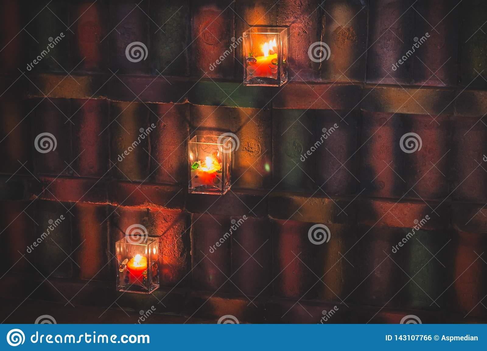 Candles in glass candlesticks illuminate a colorful wall in vintage style