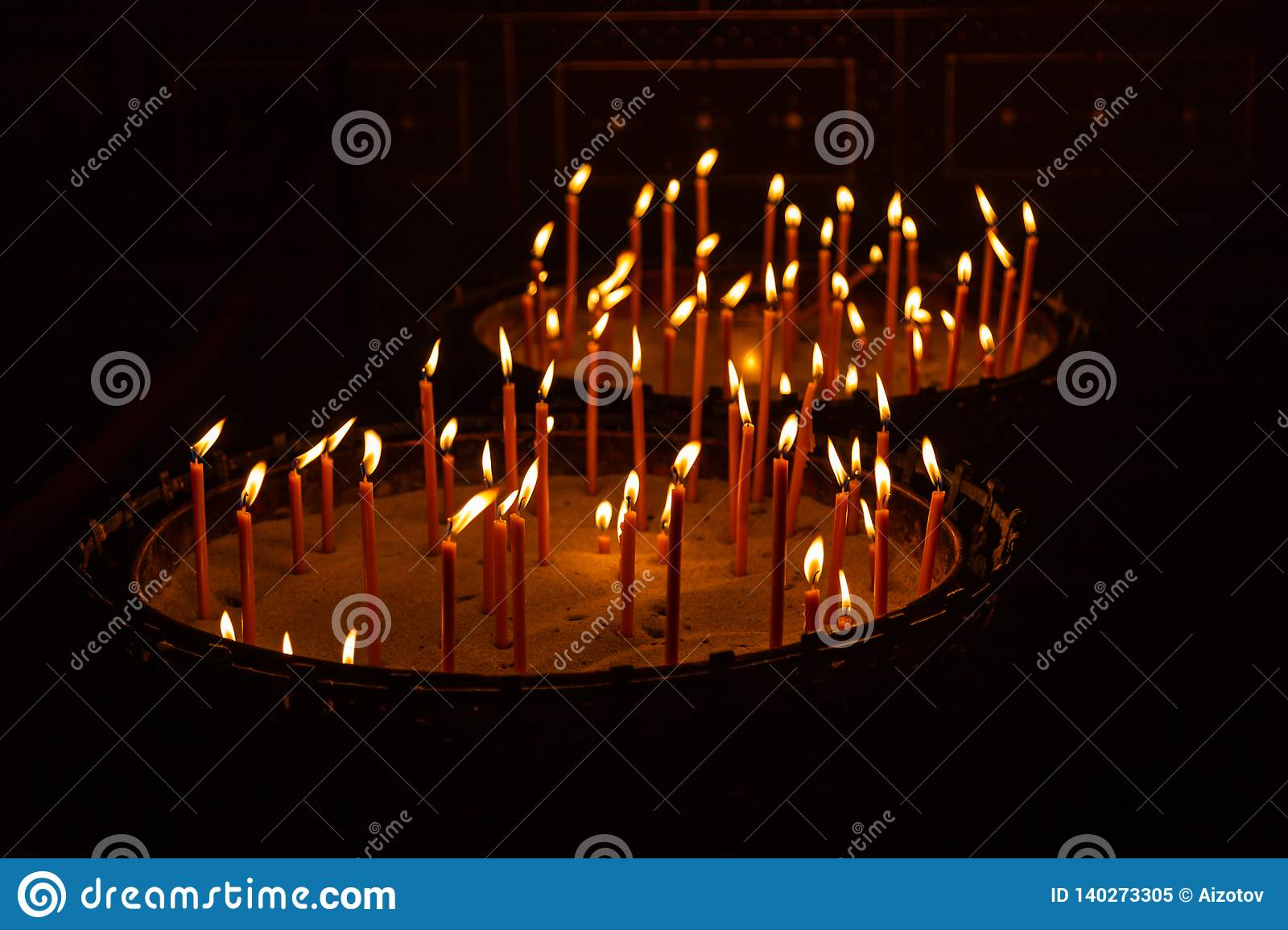 Candles lit in a stand with sand in a church in Prague