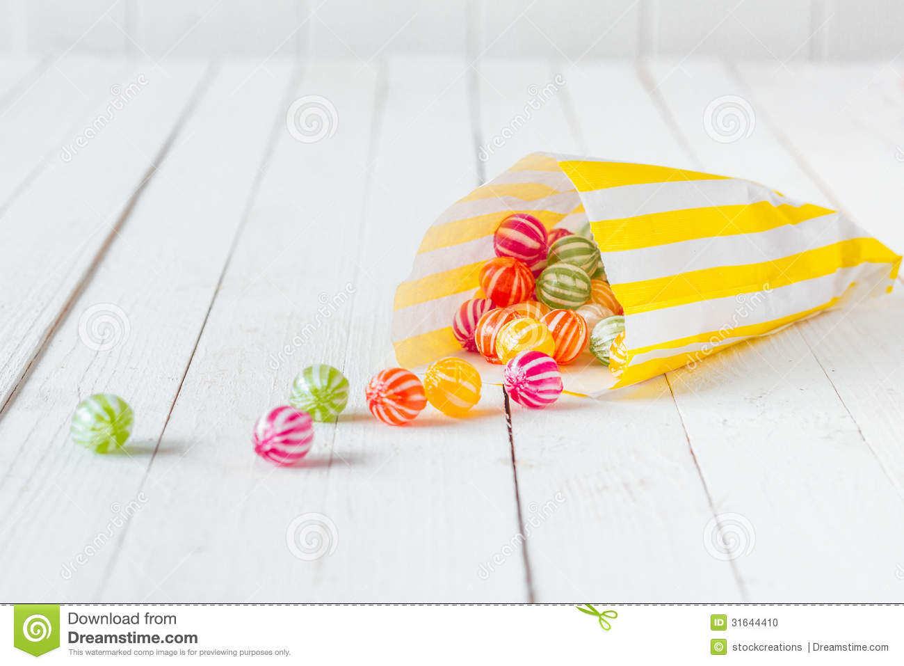 Candy bag spilling the candies over a white table stock photo image