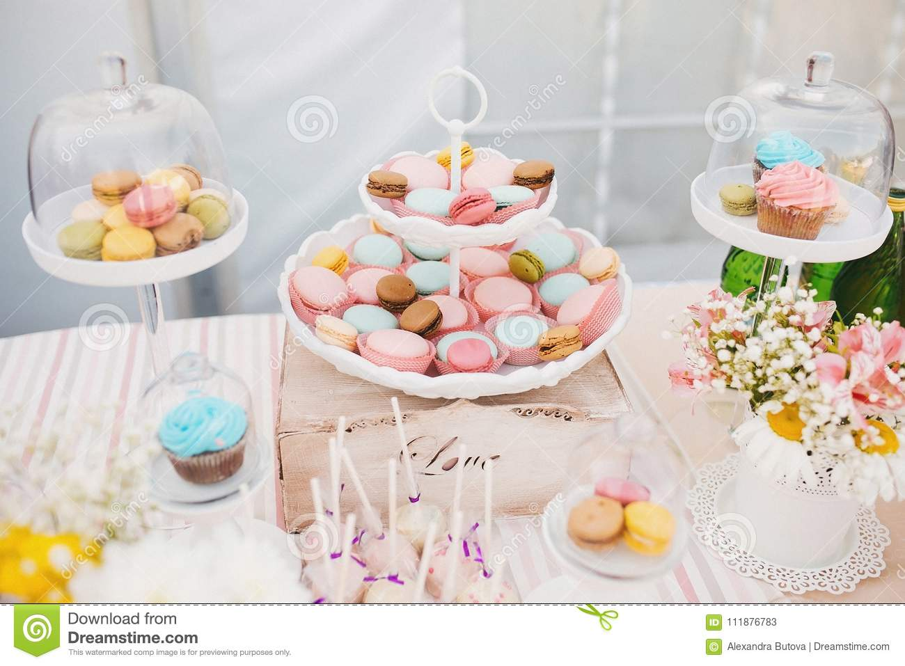Candy bar with ceramic white plate stands with colorful tasty macaroons, pink and blue cupcake on a buffet table