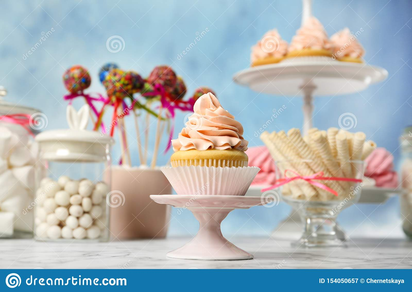 Candy bar with different sweets on white marble table