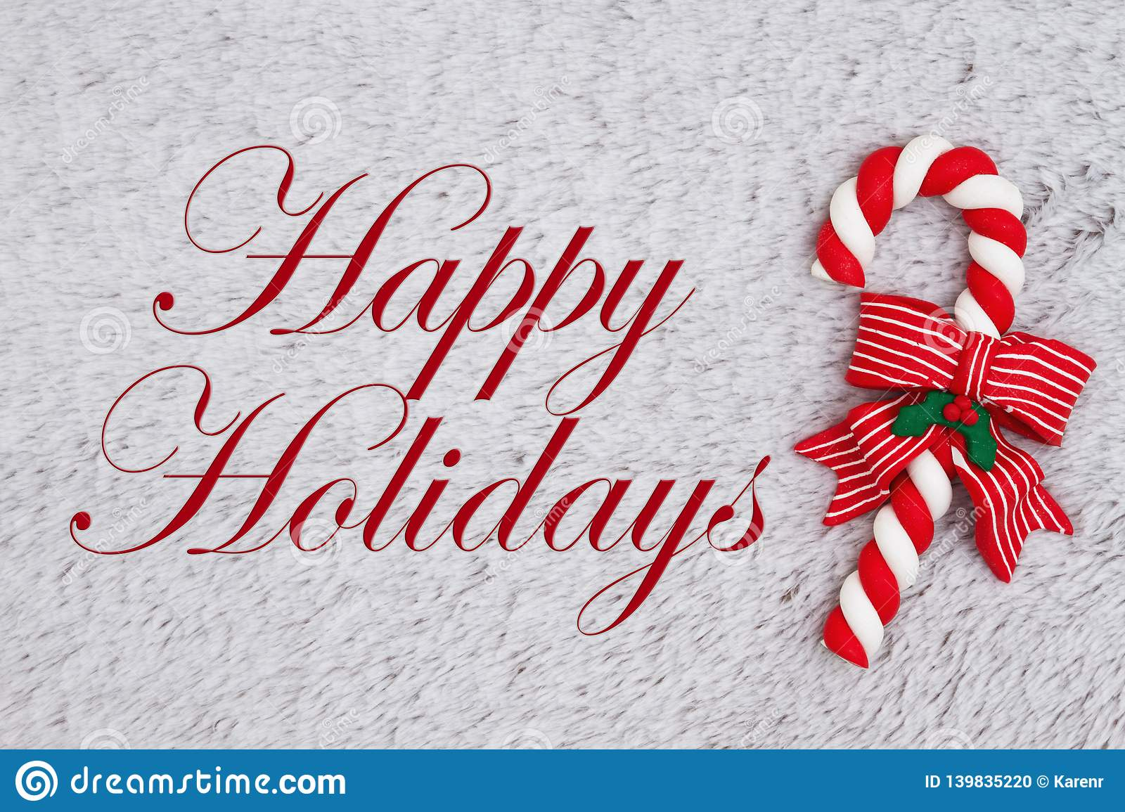 Candy cane on plush gray material with text Happy Holidays