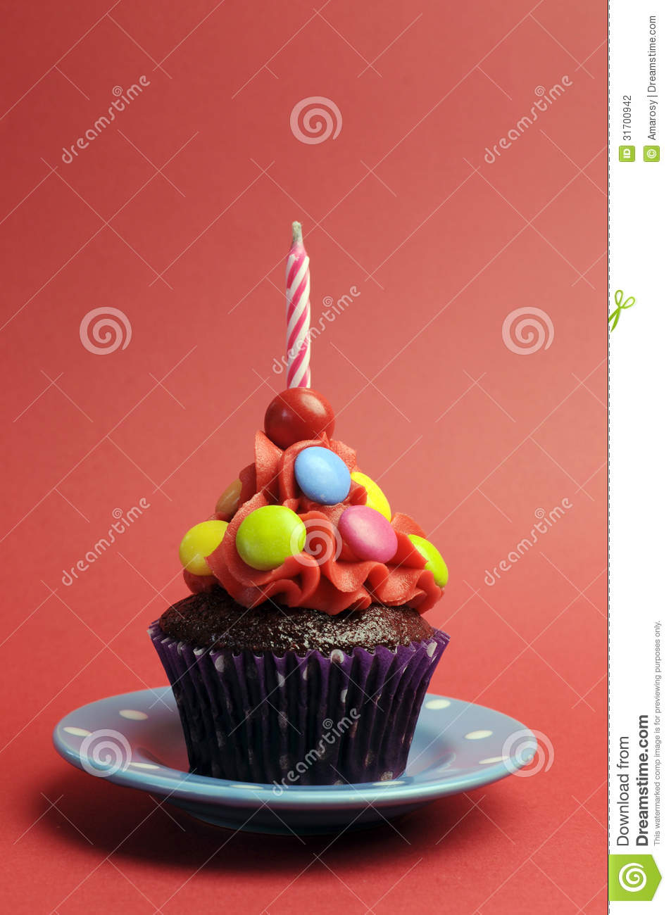 candy covered chocolate cupcake with red frosting and