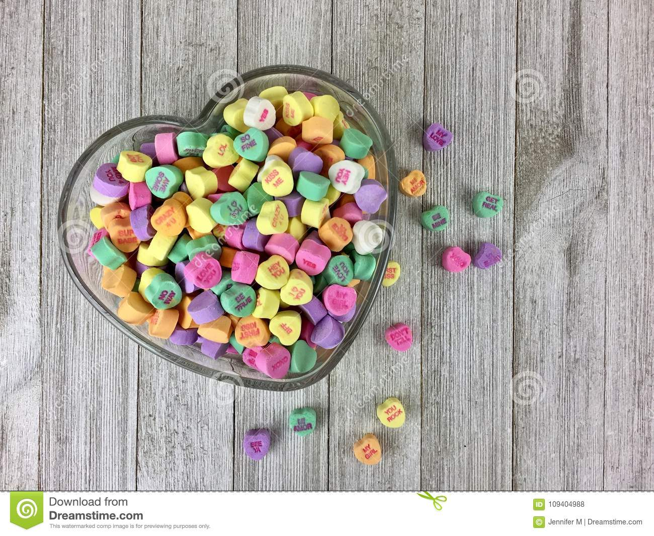 Candy hearts in a heart shaped bowl