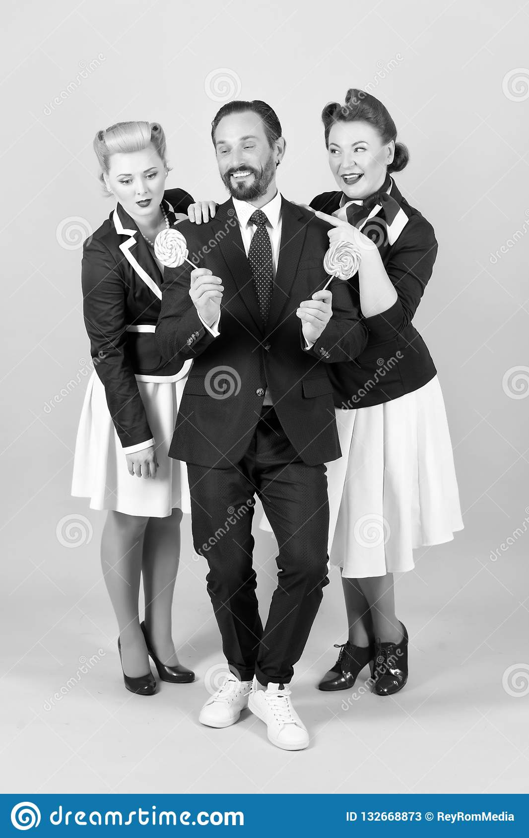 Candy man with two women and lollipops on gray background in stuido